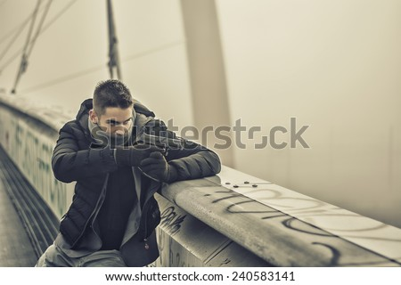 Well dressed handsome young detective or policeman or mobster standing in an urban environment aiming a firearm off to the right of the frame with a determined expression, side view - stock photo