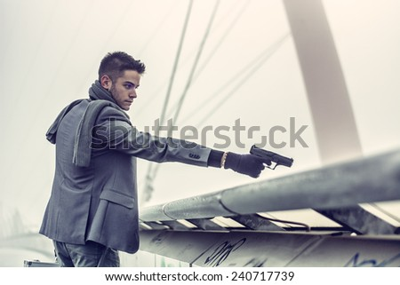 Well dressed handsome young detective or policeman or mobster standing in an urban environment aiming and firing a gun over a bridge edge - stock photo