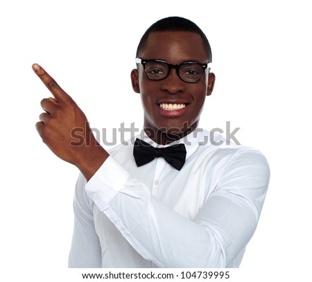 Well dressed happy young person pointing away at copy space - stock photo