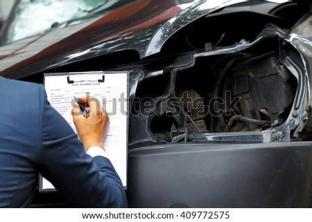 Well dressed insurance assessor inspecting damaged vehicle - stock photo