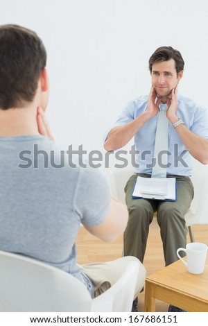 Well dressed male doctor in conversation with patient in the medical office
