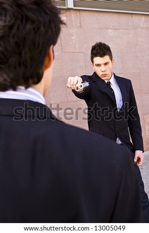 Well dressed man aiming to another with a gun - stock photo