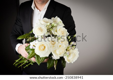 well-dressed man holding a bouquet of flowers. Holidays and celebrations. Valentines day. - stock photo