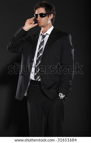 Well Dressed Man on Cell Phone Wearing Sun Glasses - stock photo