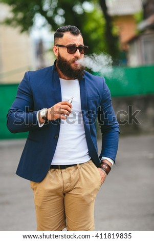 well-dressed man smoking electronic cigarette - stock photo