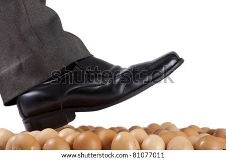Well dressed man walking on egg shells, white background. - stock photo