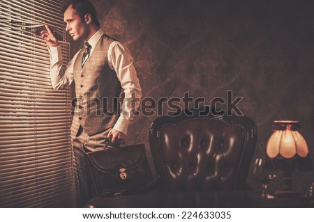 Well-dressed man with a briefcase looking through jalousie  - stock photo