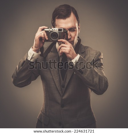Well-dressed man with a retro camera - stock photo