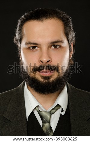 well-dressed man with beard on black background