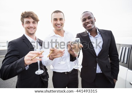 Well dressed men drinking champagne next to a limousine on a night out