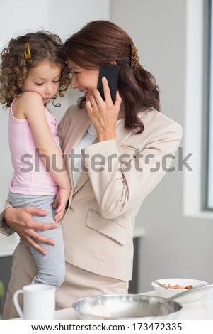 Well dressed mother carrying daughter while on call in the kitchen at home