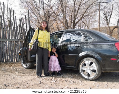 Well dressed Native American woman with a laptop standing by her car and holding her daughter's hand - stock photo