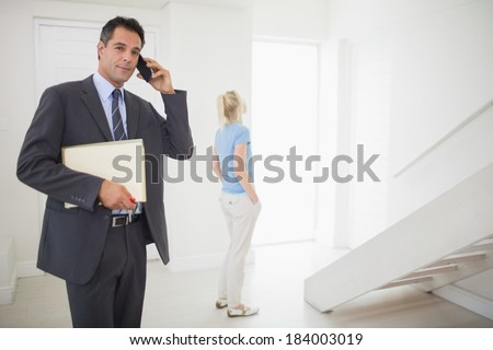 Well dressed real estate agent on call with blurred woman in the background - stock photo