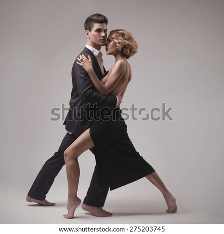 Well-dressed retro couple dancing tango over grey studio background