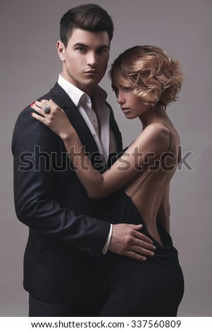 Well-dressed retro couple over grey studio background