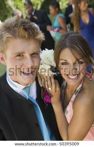 Well-dressed teenage couple standing outside school dance, elevated view - stock photo