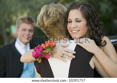 Well-dressed teenagers hugging outside - stock photo