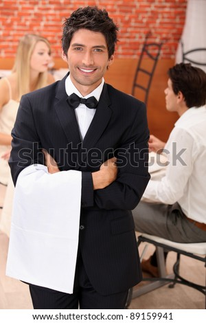 well dressed waiter facing the camera, behind a couple is dining at restaurant - stock photo
