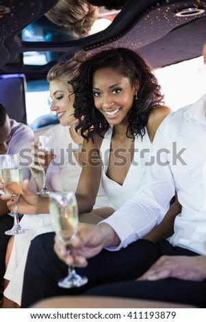 Well dressed woman drinking champagne in a limousine on a night out - stock photo