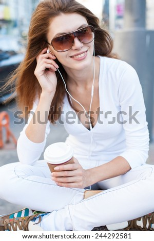 Well dressed woman drinking coffee and listening to the music / photography of young Caucasian woman wearing sunglasses with disposable cup  - stock photo