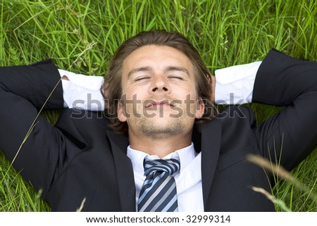 Well-dressed young businessman is resting in a field - stock photo