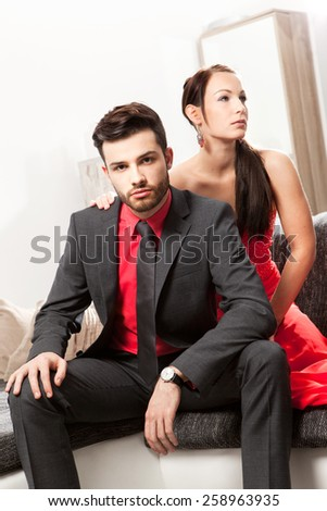Well dressed young couple sitting on a couch