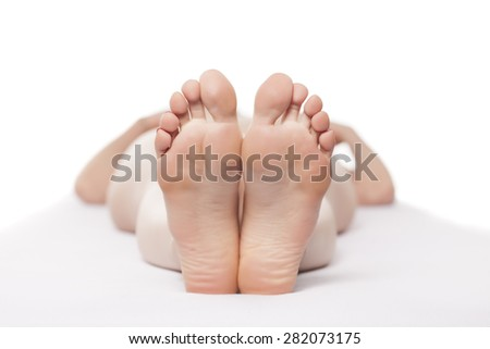 well-groomed female feet on a white sheet