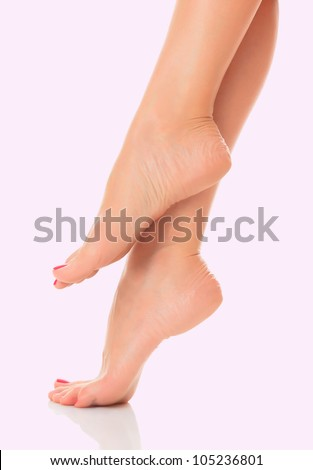 Well groomed female feet on pink background - stock photo