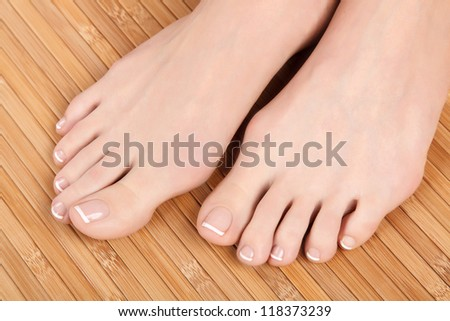 Well-groomed female feet on wooden floor - stock photo