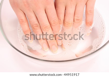 Well-groomed female hands in  glass bowl with soap water