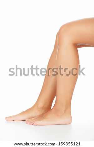Well-groomed female legs, white background, copyspace - stock photo