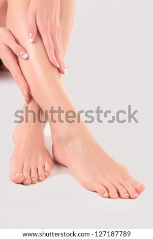 Well-groomed hands on female feet. Main focus is on the hands - stock photo