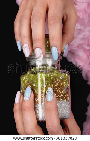 Well-groomed nail art design. pink blue and white colors of nail art. Nail polish. Beauty hands. Fashion Stylish Fashion Colorful Nails. Female hands holding a glass jar with beads. - stock photo