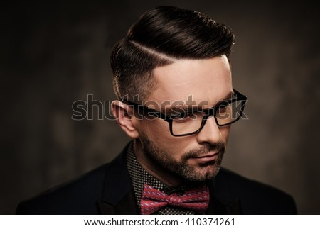 Well-groomed stylish young man with bow tie posing on dark background.
