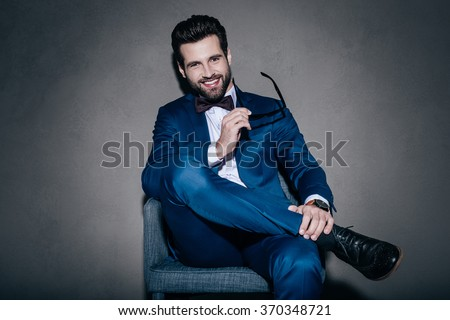 Well hello! Cheerful young handsome man in suit holding his sunglasses and looking at camera with smile while sitting on the chair against grey background - stock photo