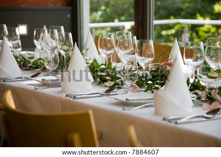 Well-laid table with white folded serviettes and wine glasses. - stock photo