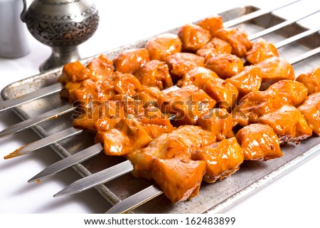 Well seasoned chicken skewers are waiting on aluminum tray, ready to go on to the grill and cook - stock photo