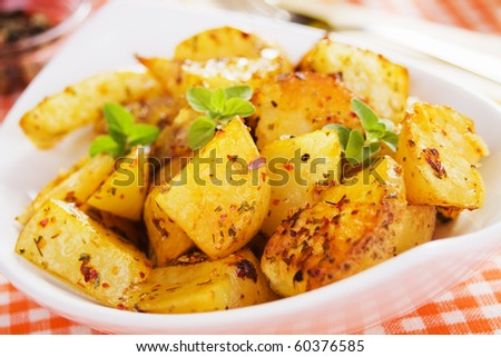 Well spiced roasted potato in white bowl - stock photo