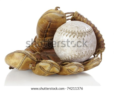 Well-used catcher's mitt with tattered softball - stock photo
