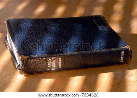 Well Used Old Bible Under Painted Light - stock photo