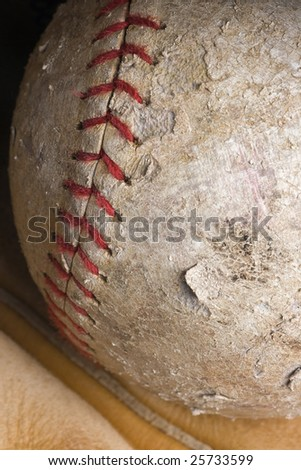 well-used softball with red stitching in mitt - stock photo