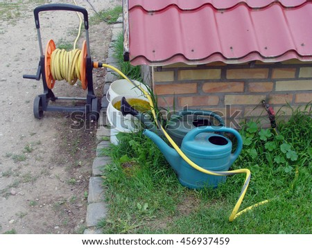 Well with watering hose roll buckets and cans on summer day.                               - stock photo