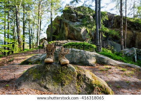 Well-worn hiking boots, unlaced and muddy on the forest floor. Tourism concept - stock photo