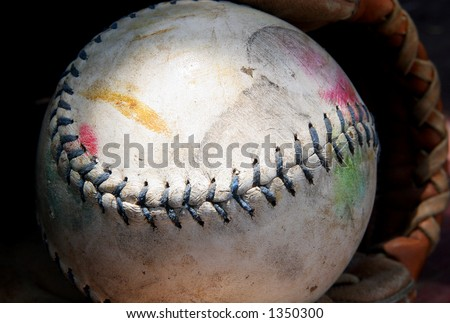 Well-worn softball in mitt - stock photo