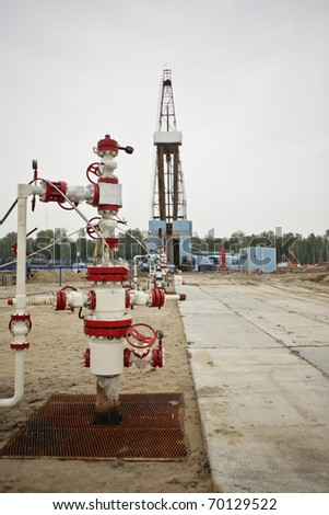 Wellhead against the rig in oifield - stock photo