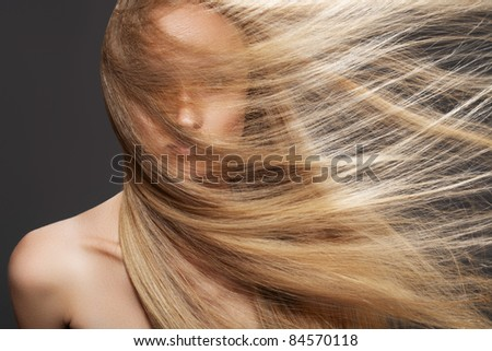 Wellness and spa. Sensual woman model with windswept flying dark blond hair on gray background. Shiny long health hairstyle. Beauty and haircare - stock photo