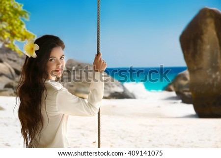 Wellness. Attractive smiling brunette girl summer portrait on exotic vacation. Beautiful sensual woman with flower in long healthy hair sitting on a swing. Good life. - stock photo