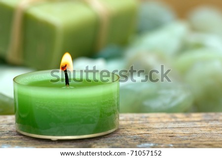 Wellness candle with soap and green stones close-up
