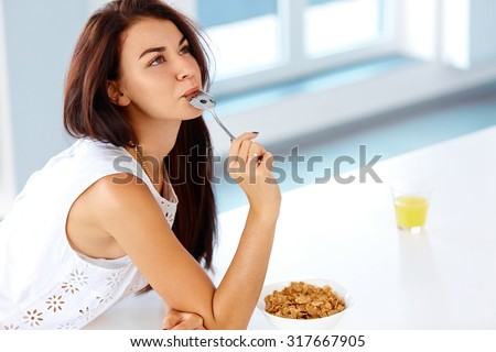 Wellness concept. Beautiful young woman  having breakfast and smiling. Healthy eating. Dieting concept. - stock photo