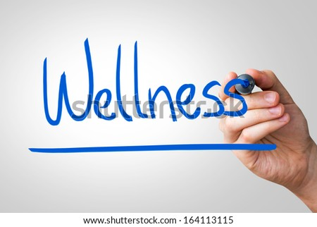 Wellness hand writing with a blue mark on a transparent board - stock photo